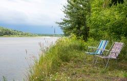 在自然的两把折叠椅,在河的河岸 库存图片