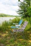 在自然的两把折叠椅,在河的河岸 免版税库存图片