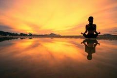 在自然的少妇实践的瑜伽,女性幸福,在海滩的少妇实践的瑜伽剪影在日落 免版税库存图片