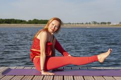 在自然的年轻女人实践的瑜伽 免版税库存图片