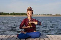 在自然的年轻女人实践的瑜伽 库存照片