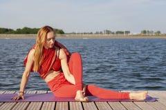 在自然的年轻女人实践的瑜伽 免版税库存照片