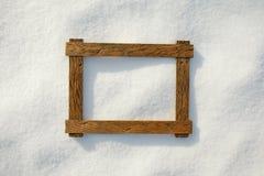 在自然雪的木制框架 免版税库存照片