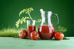 在自然绿色背景的新鲜的西红柿汁  免版税库存图片