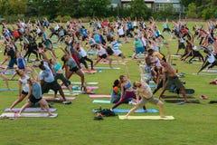 在自由室外亚特兰大瑜伽类的数十人民舒展 库存照片