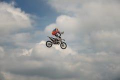 在自由式摩托车越野赛的专业车手执行在蓝色云彩天空的背景的一个把戏 德语Stuntdays,策尔布斯特- 免版税图库摄影