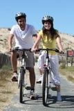 在自行车乘驾的新夫妇 库存照片