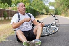 在自行车事故以后的酸疼的人在沥青 免版税库存图片
