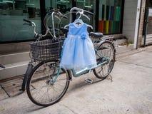 在自行车的可爱宝贝浅蓝色和白色礼服吊 免版税库存照片