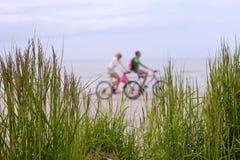 在自行车的夫妇沿海滩乘坐 免版税库存图片