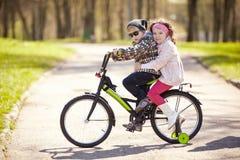 在自行车的女孩和男孩骑马 免版税图库摄影