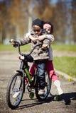 在自行车的女孩和男孩骑马 库存照片