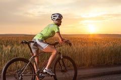 在自行车的妇女步行在乡下 免版税库存照片