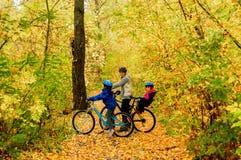 在自行车的家庭在秋天公园,父亲和孩子循环 免版税库存照片