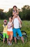 在自行车的家庭在草地 库存图片
