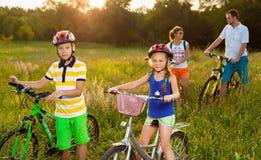 在自行车的家庭在草地 免版税图库摄影