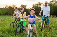 在自行车的家庭在草地 免版税库存照片