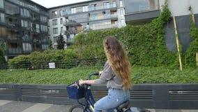 在自行车的少妇骑马在晴天 美好的心情射击了少妇或女孩骑马自行车在城市 有cerly头发的女孩 股票录像
