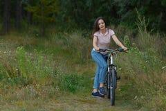 在自行车的年轻俏丽的妇女骑马在森林骑自行车者步行在公园,活跃健康生活方式 图库摄影