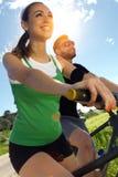 在自行车的愉快的年轻夫妇在乡下乘坐 免版税库存照片