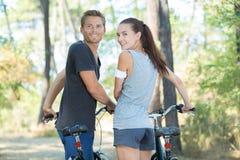 在自行车的愉快的年轻夫妇在乡下乘坐 图库摄影