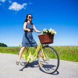 在自行车的愉快的滑稽的少妇骑马有被举的腿的 免版税库存照片