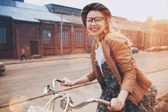 在自行车的时髦的妇女骑马 免版税库存图片