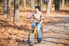 在自行车的男孩骑马在秋天公园,明亮的晴天,在背景的下落的叶子 免版税图库摄影
