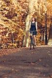在自行车的红发女孩骑马在秋季公园 免版税库存图片