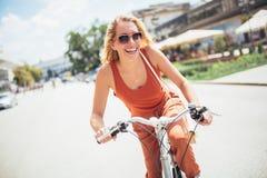 在自行车的美好的妇女骑马 库存图片