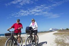 在自行车的资深夫妇乘坐,当在巡航假期时 免版税库存照片