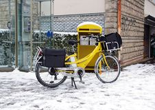 在自行车的邮政递送在冬天 免版税库存照片