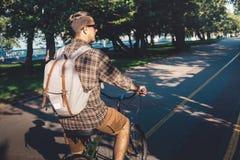 在自行车的年轻人骑马在夏天公园,行动的,背面图骑自行车者 生活方式都市休息的概念 库存照片