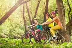 在自行车的活跃微笑的家庭在晴朗的森林里 库存照片