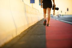 在自行车道路的妇女步行有照相机的在晚上 免版税库存图片