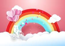在自行车飞行的甜夫妇与彩虹和云彩 图库摄影