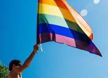在自豪感的白种人激动的同性恋者挥动的彩虹旗子 免版税库存图片
