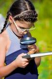 在臭虫的女孩神色与放大镜和书 免版税库存照片