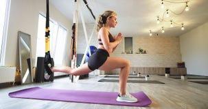 在舒展腿有有弹性支持的一个现代被装备的瑜伽演播室夫人,当坐体育席子佩带时 股票视频