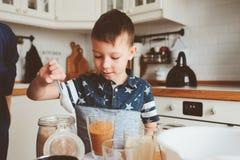 在舒适现代白色厨房里哄骗男孩面团为松饼做准备 库存图片