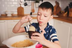在舒适现代白色厨房里哄骗男孩面团为松饼做准备 免版税库存照片