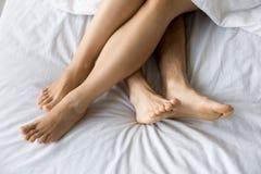 在舒适的床上的女性和男性脚,特写镜头顶视图 免版税图库摄影