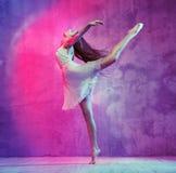 在舞池上的灵活的年轻跳芭蕾舞者