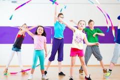 在舞蹈课traninng的孩子与围巾 免版税图库摄影
