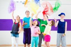 在舞蹈课traninng的孩子与围巾 免版税库存照片
