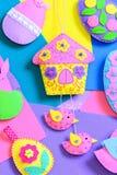 在舱内甲板的五颜六色的毛毡复活节工艺感觉板料 毛毡复活节彩蛋,有鸟的房子,兔宝宝装饰 背景逗人喜爱的复活节 免版税库存照片