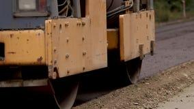 在舱内甲板的摊铺机搬家工人最近做了路,猛撞和成水平 涂柏油应用在被修理的城市道路的摊铺机沥青 股票视频