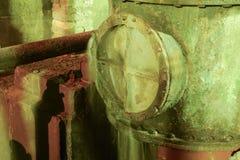 在舱口盖的漏出在管子 老设备 w的地下室 免版税图库摄影