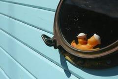 在舷窗的两只黄色鸭子 木船 免版税库存照片