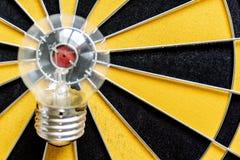 在舷窗的大电灯泡目标有掷镖的圆靶背景 免版税库存图片